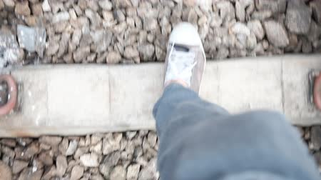 Top view of feet walking on railway with unstable camera