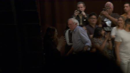 kandidát : Bernie Sanders Waves Goodbye. Bernie Sanders waves and exits the stage as the crowd cheers him on. June 2nd, 2018 at the Rally for Justice in downtown Los Angeles, California.
