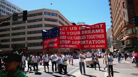 illegal alien : Citizenship Banner. A large red picket banner that reads, Citizenship For 11 Million. Let Us Be Part of Your Dreams. Keep Our Families Together. Stop Deportation. Start the Amnesty, Not the War!!! is held up and carried by multiple people during an immi Stock Footage