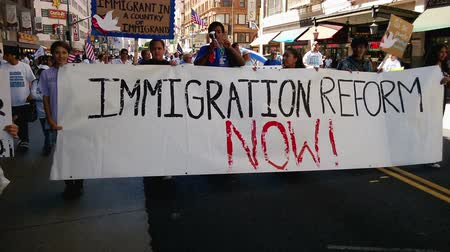 illegal alien : Immigration Reform Banner. A large white picket banner that reads, Immigration Reform Now! is held up and carried by multiple people during an immigration rally in downtown Los Angeles on September 22, 2013. Stock Footage