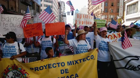 göçmen : Picket Signs and Banners at Immigration Rally. Hundreds of people, young and old, chant in Spanish while waving American flags and other signs in the air calling for the government to change and listen during an immigration rally in downtown Los Angeles o Stok Video