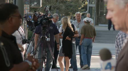 adli : Media News Reporters. News crews, reporters, and police stand by outside a City Hall rally in downtown Los Angeles, California on July 16th, 2013. Stok Video