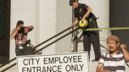 blm : City Hall Police Tape. A police officer sections off a restricted area with yellow police tape outside City Hall in downtown Los Angeles, California on July 16th, 2013. Stock Footage