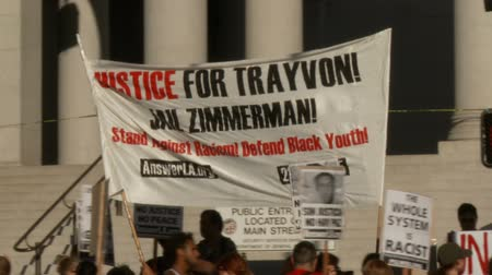 blm : JAIL ZIMMERMAN Sign. Protesters urging JUSTICE FOR TRAYVON at a rally held at City Hall in downtown Los Angeles, California on July 16th, 2013. Stock Footage