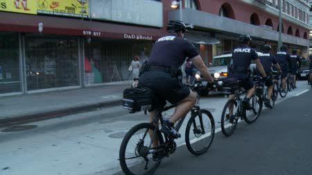 blm : Police Follow Protest on Bikes. Police officers follow protesters on bike at a rally in downtown Los Angeles, California on July 16th, 2013. Stock Footage