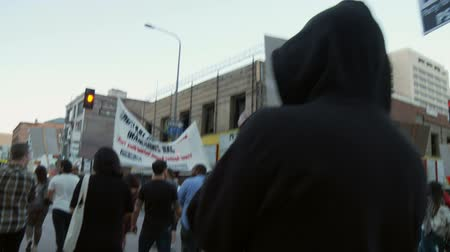 madde : SYSTEM IS RACIST Rally Sign. A sign is hoisted in the air as the crowd cheers and chants at a rally for Trayvon Martin in downtown Los Angeles, California on July 16th, 2013. Stok Video