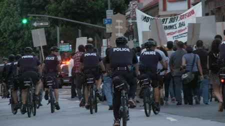 blm : Police Tail Injustice Rally. Police follow the crowd at the end of a rally for Trayvon Martin in downtown Los Angeles, California on July 16th, 2013. Stock Footage