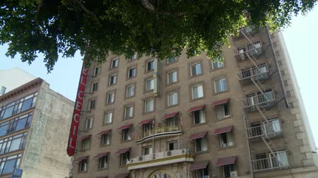 serial : Cecil Hotel Wide. Three-quarter wide shot of the Cecil Hotel as the camera tilts up to the building with a tree in the foreground and back down. Built in the 1920s, the Cecil Hotel in Downtown Los Angeles has become known for criminal activity including s Stock Footage