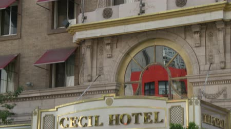 убивать : Cecil Hotel Entrance Sign. With trees in the foreground, the camera tilts between the windows of the building and the Cecil Hotel sign above the entrance. Built in the 1920s, the Cecil Hotel in Downtown Los Angeles has become known for criminal activity