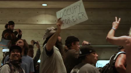 political speech : OCCUPY FOREVER Rally Signs. Pans from a man with an OCCUPY FOREVER sign to another that reads ART IS NOT CRIME at an Occupy Wall Street drum circle in downtown Los Angeles on on Feb 9, 2012.