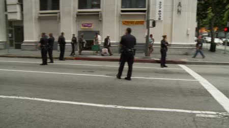 investigar : LAPD Officers Create Blockade. Officers wait at a blockade for protesters of the Occupy Movement in downtown Los Angeles, California on May 1st, 2012.
