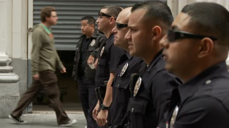 investigar : LAPD Officers Watch Protest. Officers wait at a blockade for protesters of the Occupy Movement in downtown Los Angeles, California on May 1st, 2012.