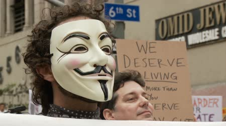 povstání : Occupy Protester Vendetta Mask. Protester wears a vendetta mask and holds a sign that reads: PEOPLE OVER PROFITS at an Occupy Rally in downtown Los Angeles, California on May 1st, 2012.