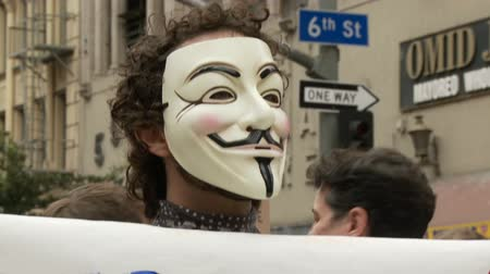 ocupação profissional : Vendetta for the People. Protester wears a vendetta mask and holds a sign that reads: PEOPLE OVER PROFITS at an Occupy Rally in downtown Los Angeles, California on May 1st, 2012.
