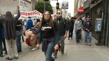 ocupação profissional : Vendetta Masked Man Walks By. Protester wearing a vendetta mask walks by at an Occupy Rally in downtown Los Angeles, California on May 1st, 2012. Stock Footage