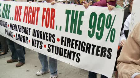 political speech : WE ARE THE 99% Sign. A sign fighting for the 99% at a rally in downtown Los Angeles, California on May 1st, 2012. Stock Footage