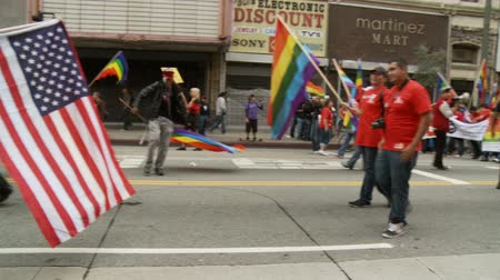 illegal alien : Waving Gay Pride Flags. People wave rainbow flags as during a march for the Occupy Movement in downtown Los Angeles, California on May 1st, 2012.
