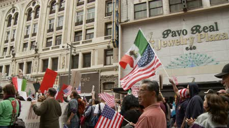 illegal alien : Crowd Waves Flags at Rally. People wave Mexican and American flags as during a march for the Occupy Movement in downtown Los Angeles, California on May 1st, 2012.
