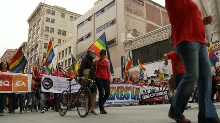 illegal alien : Los Angeles LGBTQ Rally. Protesters and immigrants with rainbow flags and banners march for gay pride in downtown Los Angeles, California on May 1st, 2012. Stock Footage
