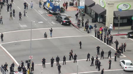 investigar : Protest Approaches Police. High angle of protesters approaching police officers in downtown Los Angeles, California on May 1st, 2012. Vídeos