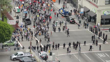 investigar : Protest Walks by Police, Wide. High angle of protesters approaching police officers in downtown Los Angeles, California on May 1st, 2012.