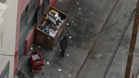 bezdomny : Homeless Man Alley. In a dumpster, a homeless man finds a pair of jeans. Note: Mans face is blurred.