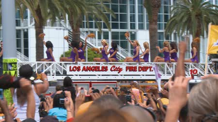pom : Laker Girls Drive By. Fans take photos as an LAFD fire truck topped with the Laker dance squad drives by the crowd at the LA Lakers NBA championship parade on June 21st, 2010, Los Angeles, California. Stock Footage