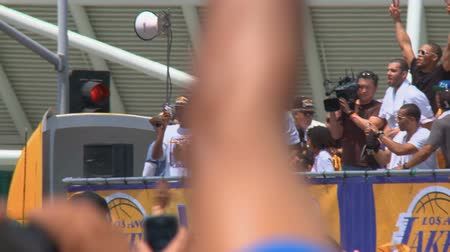 династия : Kobe Bryant Fist Pump. 2009-2010 NBA MPV Kobe Bryant hoists the championship trophy in the air as the bus with the players and team staff drives by the crowd. June 21st, 2010, Los Angeles, California. Стоковые видеозаписи