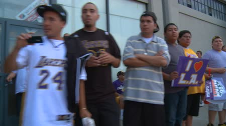 династия : Laker Fan Lineup. Fans cheer along a sidewalk as they wait to glimpse the Lakers Championship parade in downtown LA near Staples Center. June 21st, 2010, Los Angeles, California.