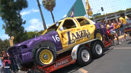 парад : LAPD Lakers Car, Zooms. An old cop car painted in the yellow, purple, and gold colors outside of Staples Center following the LA Lakers Championship parade on June 21st, 2010, Los Angeles, California. Стоковые видеозаписи