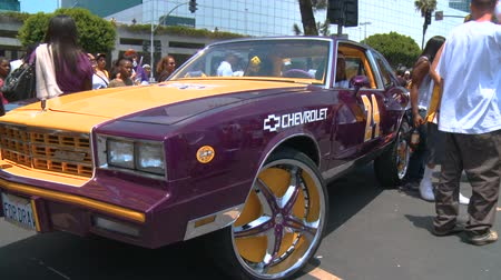 fanatics : Laker Fans Car. Fans take pictures in front of a classic Chevy Monte Carlo painted in yellow, purple, and gold following the Championship parade on June 21st, 2010, Los Angeles, California.