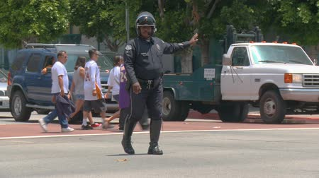 keeper : LAPD Cop Directs Traffic. A police officer directs traffic at an intersection in downtown LA after the 2010 Los Angeles Lakers championship parade. June 21st, 2010, Los Angeles, California.
