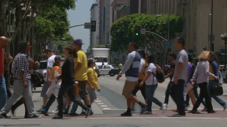 Laker Pedestrians, Wide Shot. Wide shot of pedestrians and fans crossing the street after the 2010 Lakers championship parade in downtown LA. June 21st, 2010, Los Angeles, California. Stock Footage