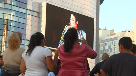Mourners at Jackson Memorial. Fans watch and take pictures of jumbotron outside Michael Jacksons memorial service at LA LiveStaples Center in downtown Los Angeles, California on July 7th, 2009. Stock Footage