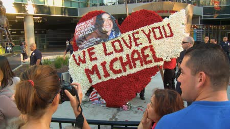 Fans Photograph Wreath. Flower arrangement reads WE LOVE YOU MICHAEL outside Michael Jacksons memorial service at LA LiveStaples Center in downtown Los Angeles, California on July 7th, 2009. Stock Footage