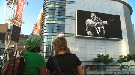 Watching Jackson Memorial Slideshow. Two fans watch jumbotron outside Michael Jacksons memorial service at LA LiveStaples Center in downtown Los Angeles, California on July 7th, 2009.
