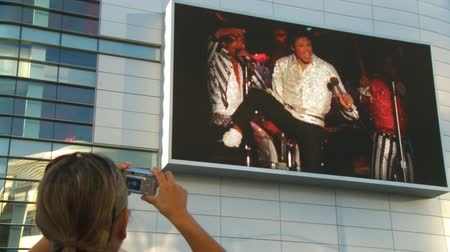 Pics of Jackson Jumbotron. A fan takes photos outside Michael Jacksons memorial service at LA LiveStaples Center in downtown Los Angeles, California on July 7th, 2009. Stock Footage