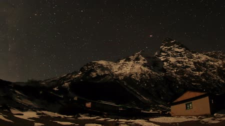 dole : Time lapse of the night sky with clouds and stars passing by behind mountain Khumbila, Dole village. Nepal, Full HD