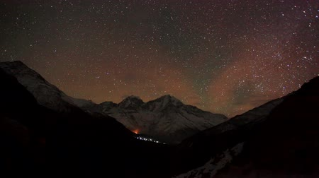 dağ geçidi : Time lapse of the night sky with clouds and stars passing by behind mountain Kongde Ri, Dole village. Nepal, Full HD