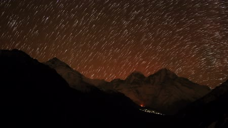 kamp : Time lapse of the night sky with clouds and stars passing by behind mountain Kongde Ri, Dole village. Nepal, Full HD
