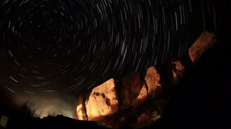 startrails : Time lapse of the night sky with clouds and stars passing by behind mountain. Cave city Eski-Kermen, Crimea. Russia. Full HD