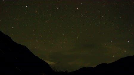 startrails : Time lapse of the night sky with clouds and stars passing by behind mountain Cho Oyu. Nepal, Full HD