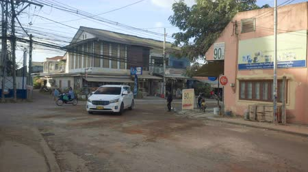 Лаос : Street in Vientiane, Laos, man wetting dust with water Стоковые видеозаписи