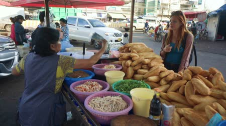 kolendra : Caucasian woman buying lao sandwiches made by lao women from fresh baguette in Vientiane Wideo