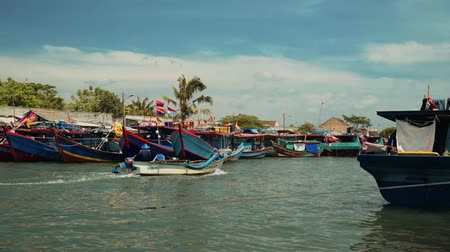 fishing village : Fishing boats sailing in river in Cilacap, Java, Indonesia on sunny summer day