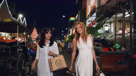 зависать : Asian and caucasian young happy smiling and talking women walking at Malioboro street in Jogjakarta, Indonesia at night Стоковые видеозаписи
