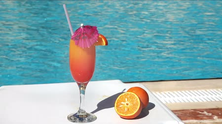 uszoda : Orange cocktail with umbrella and straw near swimming pool Stock mozgókép