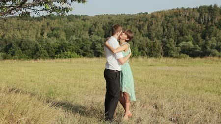 sarılmak : Young couple hugging on the yellow grass Stok Video