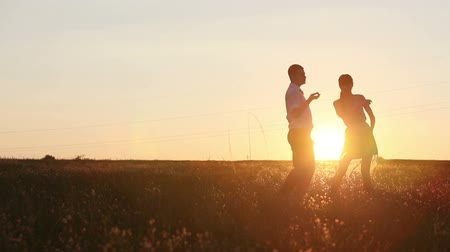 baví : Young couple silhouettes dancing on the field at sunset