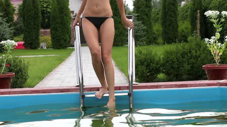 yüzme havuzu : Pretty girl in bikini stepping down swimming pool stairs